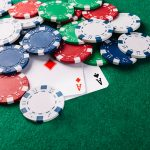 Poker cars and chips on green gambling table